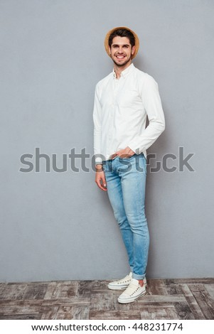 Full length of happy handsome young man in white shirt, jeans and hat standing over grey background