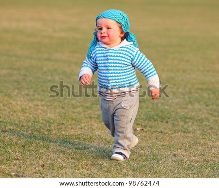Full length of happy little boy running in garden with mouth open - stock photo