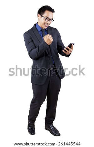 Full length of happy male manager reading a good news on his cellphone, isolated on white - stock photo