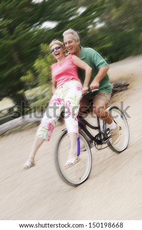 Full length of happy man riding bicycle while woman sitting on handlebar - stock photo