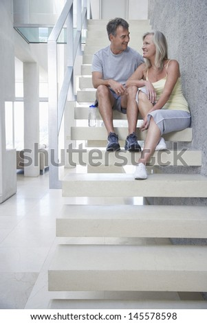 Full length of happy middle aged couple sitting on steps - stock photo