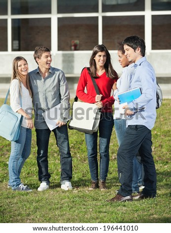 Full length of happy multiethnic students standing on college campus - stock photo