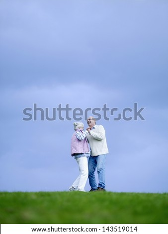 Full length of happy senior couple dancing on field - stock photo