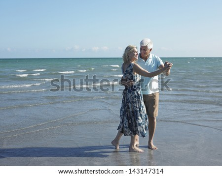 Full length of happy senior couple dancing on tropical beach - stock photo
