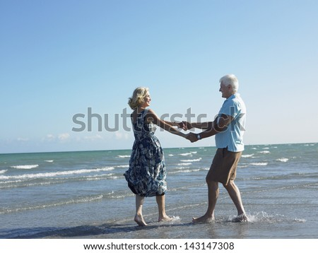 Full length of happy senior couple holding hands and dancing on tropical beach - stock photo