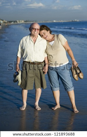 Full length of happy senior couple spending leisure time together on beach - stock photo
