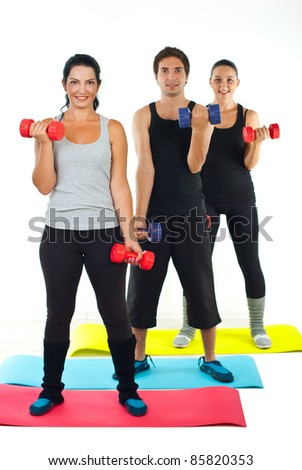 Full length of happy team of people doing fitness and working with dumbbell on colorful mats - stock photo