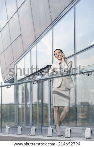 Full length of happy young businesswoman using cell phone at office balcony - stock photo