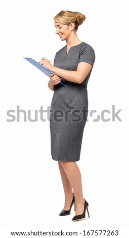 Full length of happy young businesswoman writing on clipboard against white background. Vertical shot.