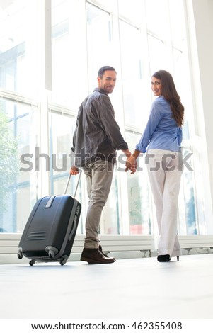 Full length of happy young couple with luggage at airport. Loving male and female partners are holding hands. They are in casuals.