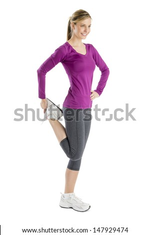 Full length of happy young woman looking away while stretching leg muscle isolated over white background - stock photo