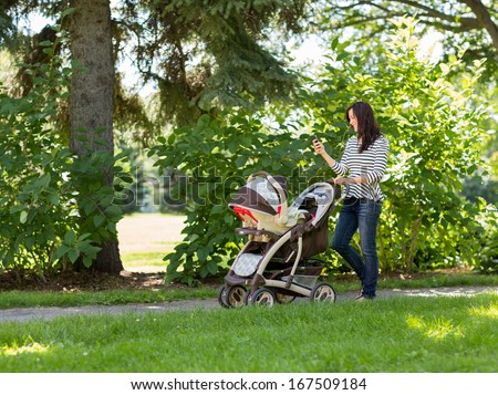 Full length of happy young woman with baby carriage using cell phone in park - stock photo