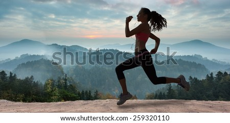 Full length of healthy woman jogging against misty landscape - stock photo