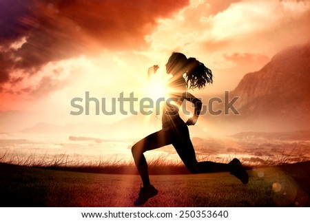 Full length of healthy woman jogging against sunrise over magical sea - stock photo
