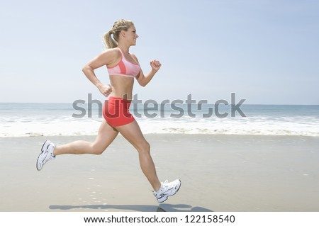 Full length of healthy young woman jogging on seashore - stock photo