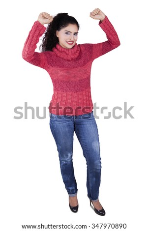 Full length of indian young woman standing in the studio while wearing winter clothes, isolated on white background - stock photo