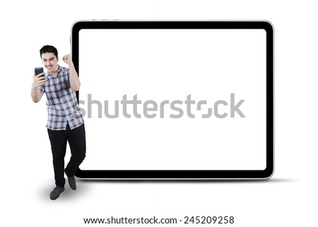 Full length of joyful young man expressing success while reading good news on the mobile phone - stock photo