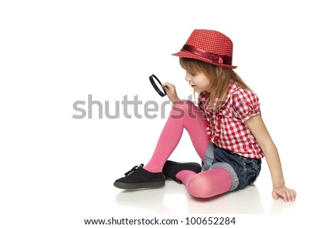 Full length of little girl sitting on the floor with magnifying glass, isolated on a white background - stock photo