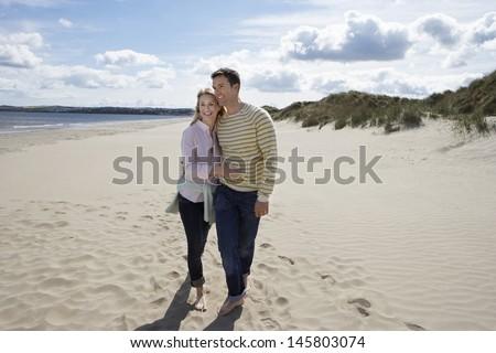 Full length of loving couple walking on sandy beach - stock photo