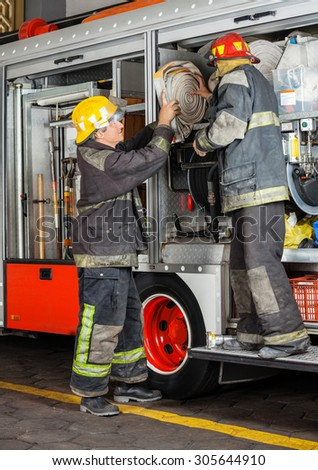 Full length of male firefighters removing hose from truck in fire station - stock photo