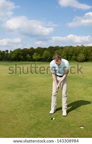 Full length of male golfer putting on green - stock photo