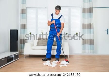 Full length of male janitor sweeping crumpled papers on floor in living room - stock photo