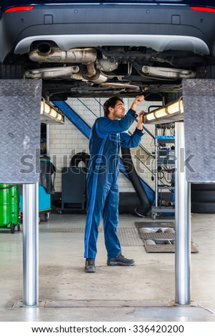 Full length of male mechanic examining under the car at garage - stock photo