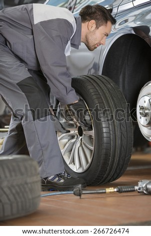 Full length of male mechanic fixing car's tire in repair shop - stock photo