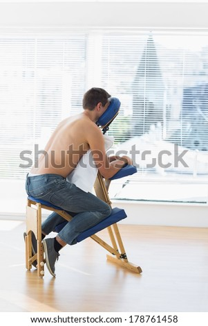 Full length of male patient sitting on massage chair in hospital - stock photo