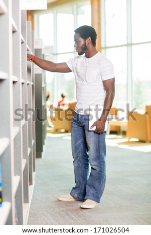 Full length of male student with digital tablet selecting book in bookstore - stock photo