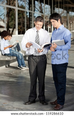Full length of male teacher and student discussing over book on university campus