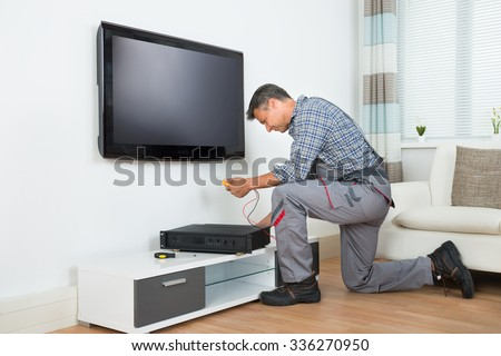 Full length of male technician installing TV set top box at home - stock photo