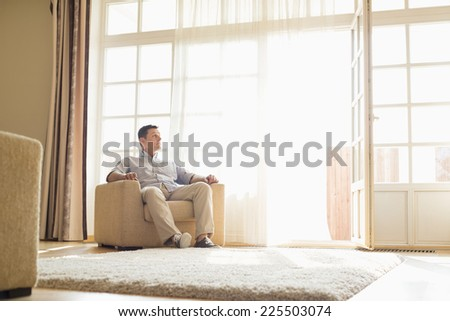 Full length of man relaxing on armchair at home - stock photo