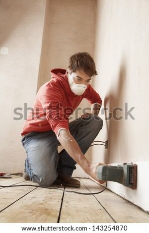 Full length of man wearing mask while sanding wall in unrenovated room - stock photo