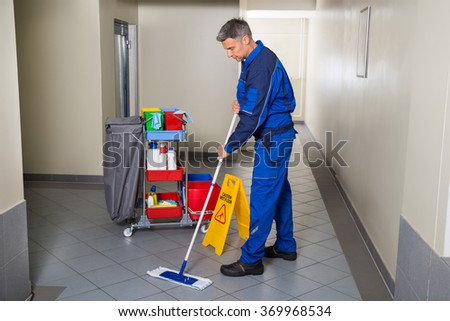 Full length of mature male worker with broom cleaning corridor - stock photo