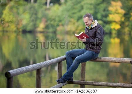 Full length of mature man reading book while sitting on fence against lake