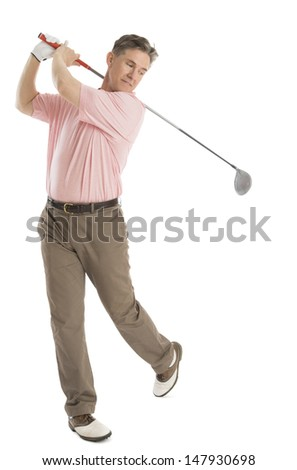 Full length of mature man swinging golf club against white background - stock photo