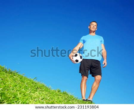Full length of mature man with football standing on meadow against clear blue sky - stock photo