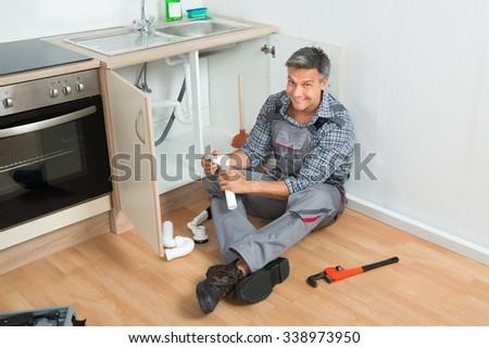 Full length of mature plumber repairing sink pipe in kitchen - stock photo