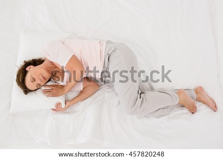 Full length of mature woman sleeping on bed at home