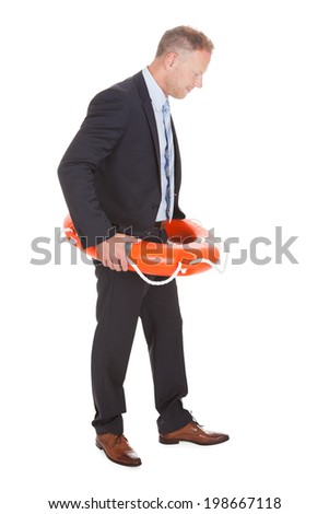 Full length of mid adult businessman with life buoy over white background - stock photo
