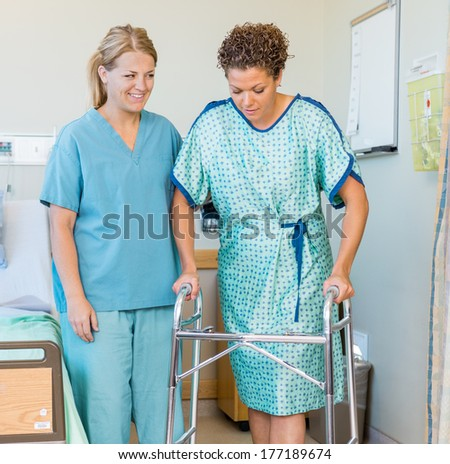 Full length of mid adult female patient walking with the help of walker while nurse looking at her in hospital - stock photo