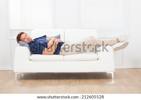 Full length of mid adult man sleeping on sofa at home