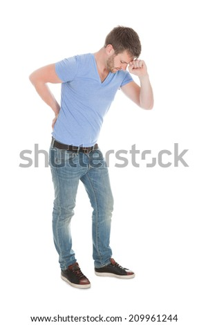 Full length of mid adult man suffering from backache over white background - stock photo