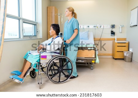 Full length of mid adult nurse with patient sitting on wheel chair at window in hospital
