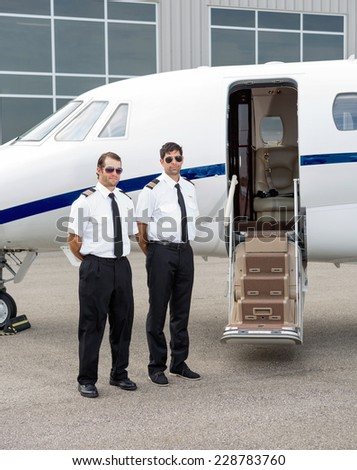 Full length of mid adult pilots standing by private jet with open door - stock photo