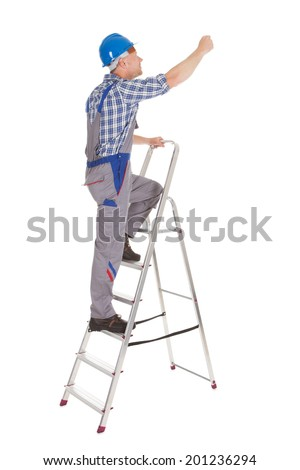 Full length of mid adult repairman climbing step ladder over white background - stock photo