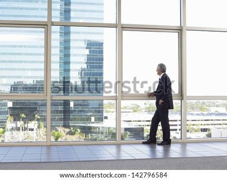 Full length of middle age businessman looking out of office window - stock photo