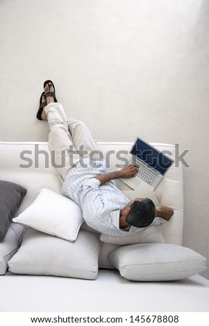 Full length of middle aged man using laptop on couch in living room - stock photo