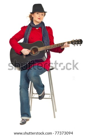 Full length of modern woman sitting on chair and playing guitar isolated on white background - stock photo